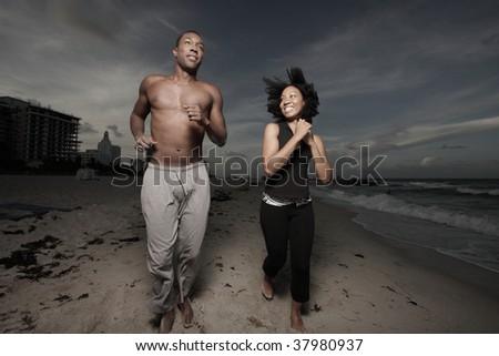 Couple running on the beach after dark - stock photo