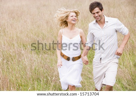 Couple running outdoors holding hands smiling - stock photo
