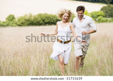 Couple running outdoors smiling - stock photo