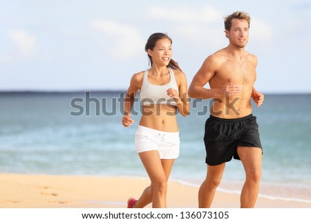 Couple running. Sport runners jogging on beach working out smiling happy. Fit male fitness model and attractive female jogger. Multiracial group, Asian woman and Caucasian man. - stock photo