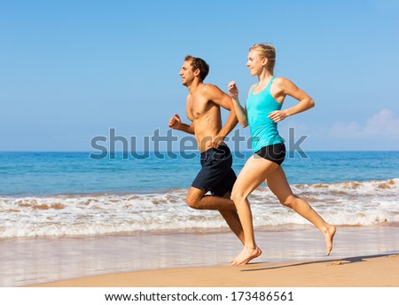 Couple running. Sport runners jogging on beach working out smiling happy. Fitness exercise concept. - stock photo