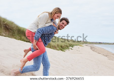 Couple Running Through Sand Dunes Together - stock photo