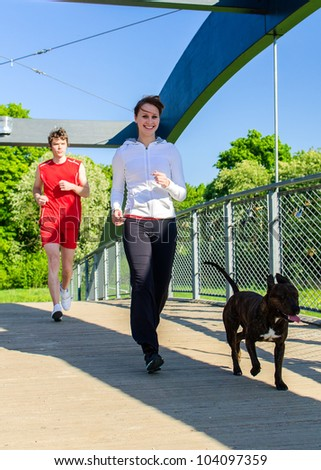 Couple running with dog across the bridge - stock photo