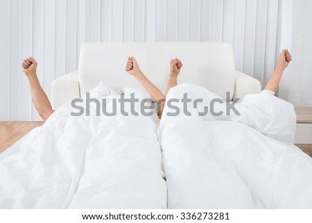 Couple's Hand Out Of Their Blanket Sleeping On Bed - stock photo
