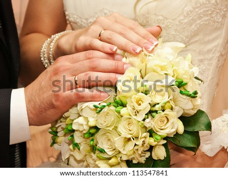 couple's hands on the bouquet