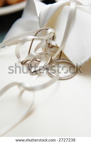 couple's wedding ring rested on a white silky sheet - stock photo