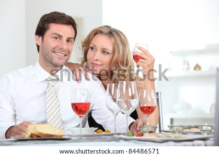 Couple sat at table with wine glasses - stock photo