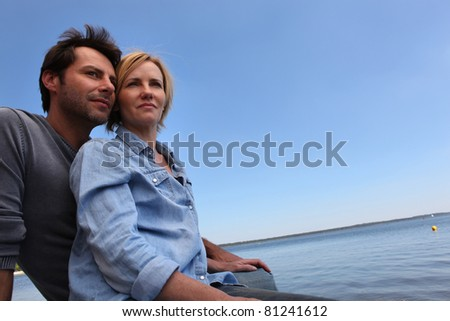 Couple sat by water - stock photo