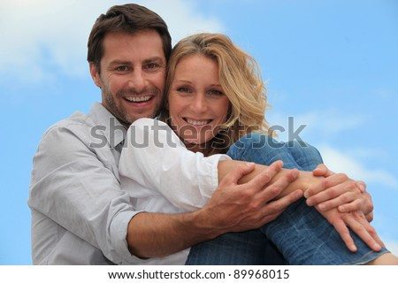 Couple sat hugging each other in park - stock photo
