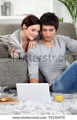 Couple sat on couch with newspaper and laptop - stock photo
