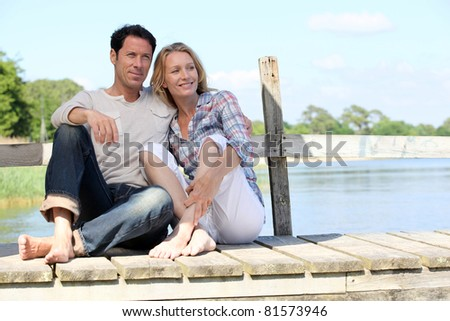Couple sat on jetty - stock photo