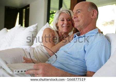 Couple sat on their veranda with laptop - stock photo
