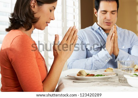 Couple Saying Grace Before Meal At Home - stock photo