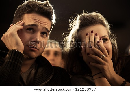 Couple scared at the cinema, watching horror movie,Italy - stock photo