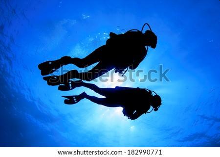 Couple Scuba Diving silhouette - stock photo