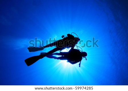 Couple scuba diving, silhouetted against sun - stock photo