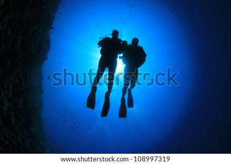 Couple Scuba Diving, silhouettes against sun - stock photo