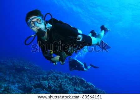 Couple Scuba Diving together over a beautiful coral reef - stock photo