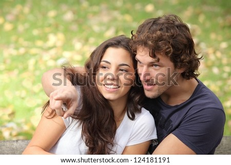 Couple seated on a bench in a park watching where the man points - stock photo