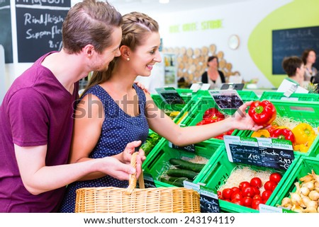 Couple selecting paprika while grocery shopping in organic supermarket  - stock photo