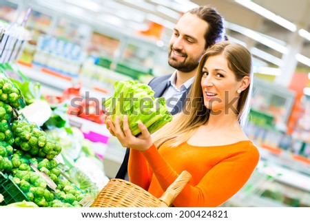 Couple selecting vegetables while grocery shopping in supermarket  - stock photo