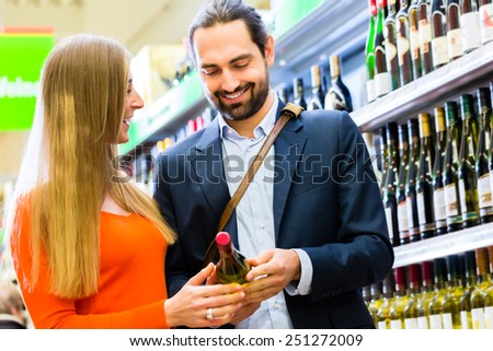 Couple selecting wine in supermarket - stock photo