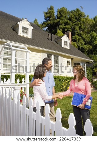 Couple shaking hands with real estate agent - stock photo