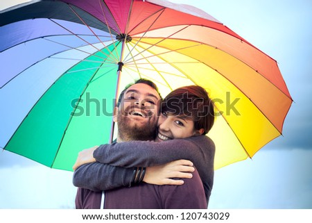 Couple sharing a moment of tenderness under the rain outdoors