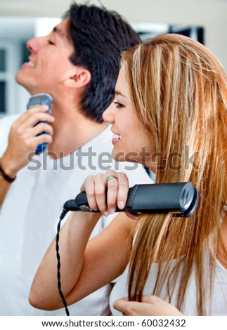 Couple shaving, brushing hair and getting ready in the morning - stock photo