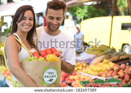 Couple shopping at open street market carrying a paper bag with a 100% organic certified label full of fruit and vegetables. - stock photo