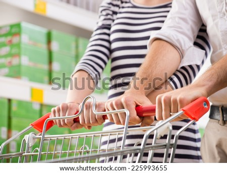 Couple shopping at supermarket hands on trolley close-up.
