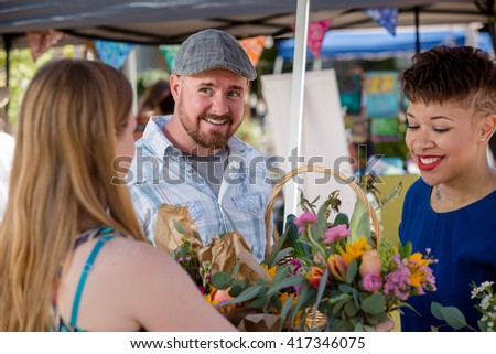 Couple shopping for flowers at outdoor farmers market - stock photo