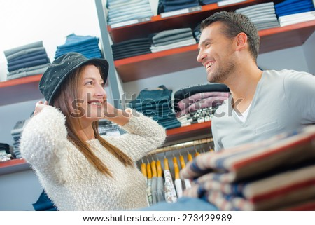 Couple shopping for hats - stock photo