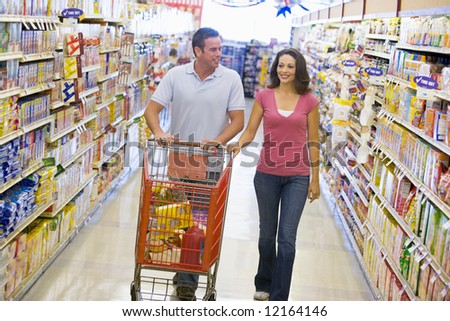 Couple shopping in supermarket grocery aisle - stock photo