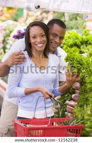 Couple shopping in supermarket produce section - stock photo