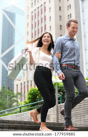 Couple shopping walking happy in Hong Kong Central. Two young fashion shoppers smiling holding shopping bags walking in city together. Asian woman and Caucasian man. - stock photo