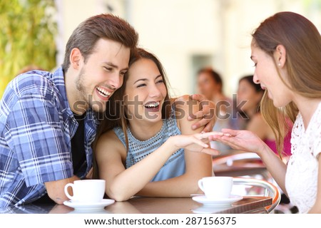 Couple showing his engagement ring to a friend in a coffee shop - stock photo