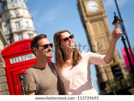Couple sightseeing in London pointing away near the Big Ben - stock photo