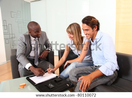 Couple signing home-purchase contract - stock photo