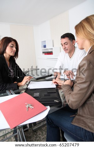 Couple signing property contract with real estate agent - stock photo