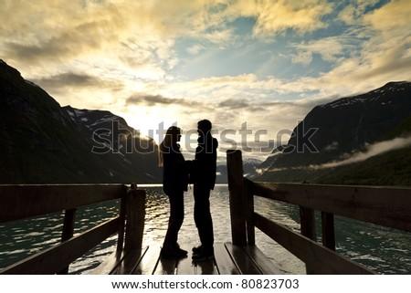 couple silhouette at mountain lake - stock photo