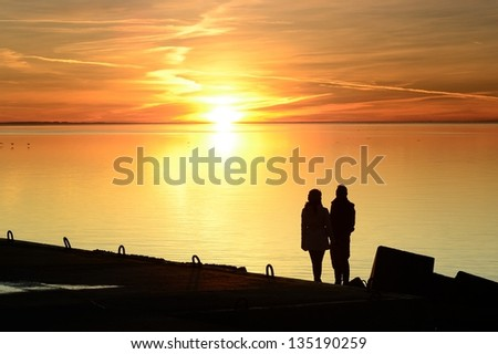 couple silhouette in the sea sunset - stock photo