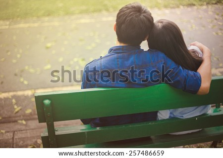 Couple sit and embrace in the garden. - stock photo