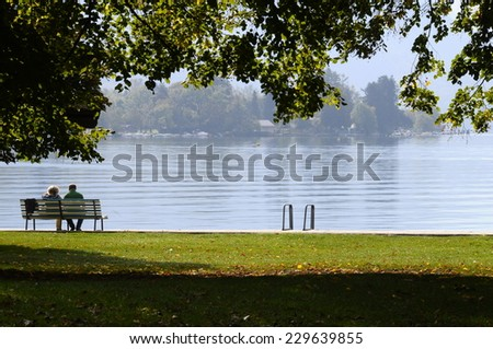 Couple sitted on bench, and Landscape of Annecy lake and mountains in Savoy, France - stock photo