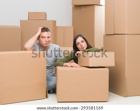 couple sitting around cardboard moving boxes, sad about leaving their home - stock photo