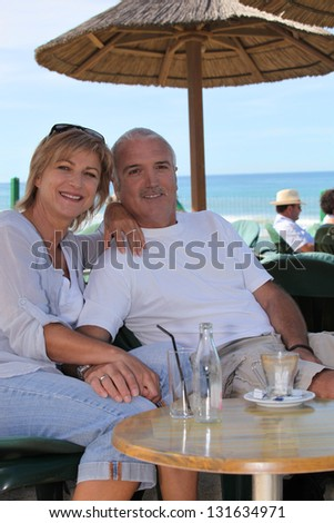 Couple sitting at a beachside cafe - stock photo