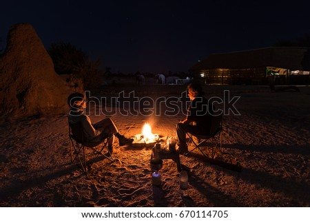 Couple sitting at burning camp fire in the night. Camping in the desert with wild elephants in background. Summer adventures and exploration in the african National Parks.