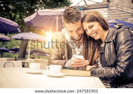 Couple sitting at restaurant table taking a self portrait with phone - Friends in a bar looking at cell phone - stock photo