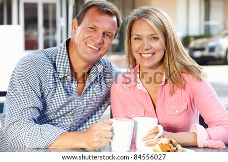 Couple sitting at sidewalk cafe - stock photo