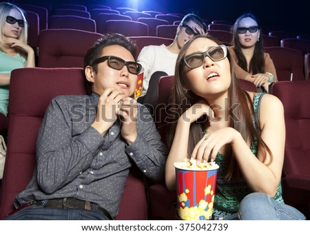 Couple sitting at the cinema, watching a horrors film. Cinema photo series - stock photo
